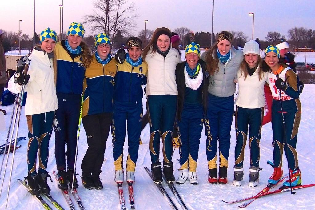 """Junior Ellen McCarthy with the Spartan Nordic Ski Team at the Jan. 9 conference meet at Battle Creek.  From left: sophomore Lexi Hilton, eighth grader Greta Sirek, senior Sela Patterson, eighth grader Dina Moradian, senior Katrina Hilton, eighth grader Val Hart, junior Ellen McCarthy, junior Mary Naas, and freshman Neeti Kulkarni. """"... the SPA team has allowed me to become a leader,"""" McCarthy said."""