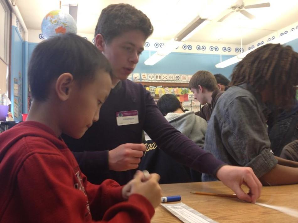 Senior Charlie Rosenblum helps his second grade friend make a name tag.