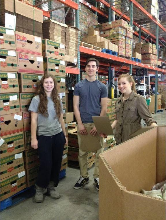 """Sophomores Ella Hommeyer, Lukas Kelsey-Friedemann, and Liza Bukingolts stands next to a pallet of boxes of tortillas they packed during their service trip to Second Harvest Heartland. """"I think it's fun because I did tortilla packing last time I was here,"""" Bukingolts said."""