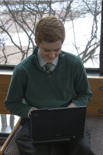 """Sophomore Cullen McCabe plays Tetris in the gym foyer. """"It's pretty simple, there's not a lot of keys that you have to hit,"""" McCabe said. """"The more you play it, the faster you can go… You always want to get a higher score."""" The game was originally released in 1984 and is often highly ranked on lists of best games."""