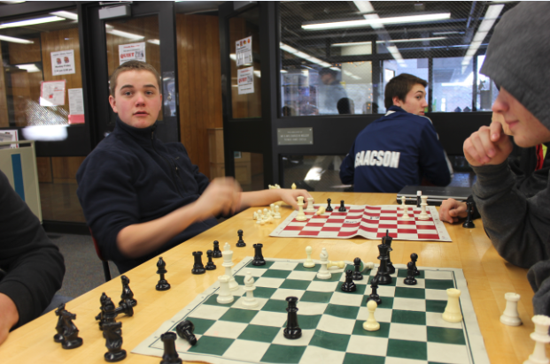 """Parallel chess games go on in the lower library, with junior Kit Rasmussen at one board and junior Jack Labovitz at the other.  """"I enjoy the stimulating intellectual competition. How it's so challenging,"""" Rasmussen said."""