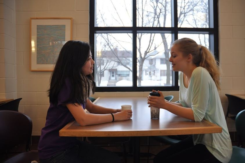 What would one see around St. Paul Academy and Summit School during the school day? Tea in hand, senior Jessica Wen chats with visitor Lotta Bublitz in the lunch room.