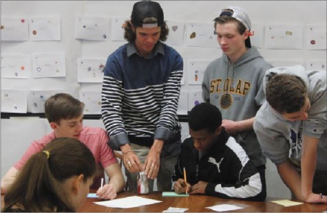 "From left: seniors Ann Hill, Josh Johnson, Dylan White, Emun Solomon, Lowell Naas, and Bryant Carlson write notes during their retreat on April 2. "" A large part of the purpose is to... acknowledge where you've come from, and acknowledge where you're going,""  SCLC advisor Eric Severson said."
