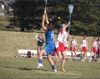 Freshman Mari Knudson fights for the ball during the first Junior Varsity lacrosse game of the season against Eagan on April 11.