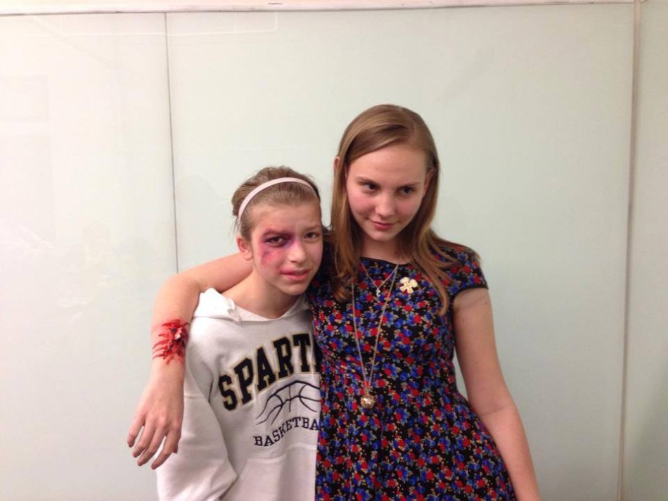 Sophomore Maren Findlay arranged a visit from make-up artist Mary K. Flaa to school as part of the ambassador program at Parl Square Theatre. Sophomore Calla Saunders and Findlay  pose with their fake injuries after the stage makeup  workshop.