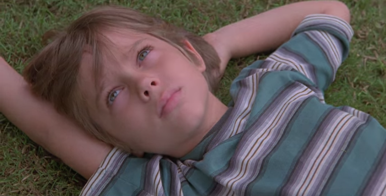 BOYHOOD OPENS WITH MASON at age six, staring up at the sky while he waits for his mom to finish talking to his teachers.