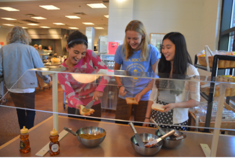 """Sophomores neeti kulkarni, Katie Brunell, and Stephanie Li use sun butter, a substitute for peanut butter under the new nut-safe policy, to make sandwhiches at lunch. """"I'm really sad but I understand as to why because it's life threatening,"""" Li said."""
