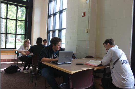 """Upperclassmen work in the lunch room during Tutorial, now with laptops since the new WiFi was installed.  """"It's nice because it is a quiet space and I get to work on group projects and get it done with wifi,"""" senior Nancy Moyers (pictured above left) said."""