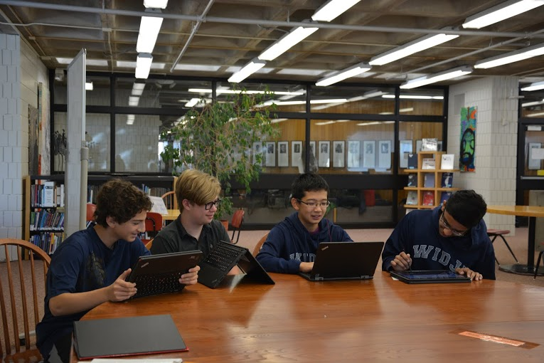 """Caption: Freshmen Ben Konstan, Tucker Waltenbaugh, Larry Chen, and Adnan Askari spend their tutorial finishing up work on their new Lenovo Thinkpad Yoga laptops. """"The keyboard gets sucked in and the buttons don't work anymore so when you swivel you aren't accidentally typing,"""" Chen explains, citing the new computer's most distinctive feature."""