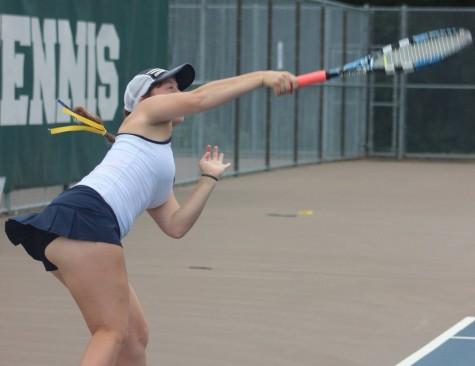 Junior Ella Hommeyer follows through with her serve against Central High School on Sep. 14.