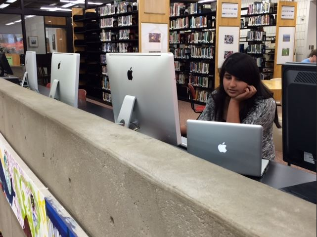 """Sophomore Tabeer Naqvi explores the programs available on the iMacs in the Upper library. """"[you can use them] when you have those projects where you have to put in pictures or make videos...compared to the computers we have now, there's so much more we can do on them,"""" she said."""