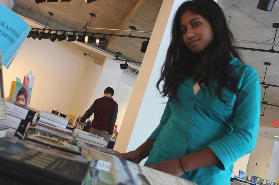 """Junior Navodhya Samarakoon browses at Bookfest to find some of the books she has on her list of must reads. """"There are a few books I really want to read at Bookfest. I Am Malala [by Malala Yousafzai ]and 1491 [by Charles C. Mann], mainly,"""" Samarakoon said."""