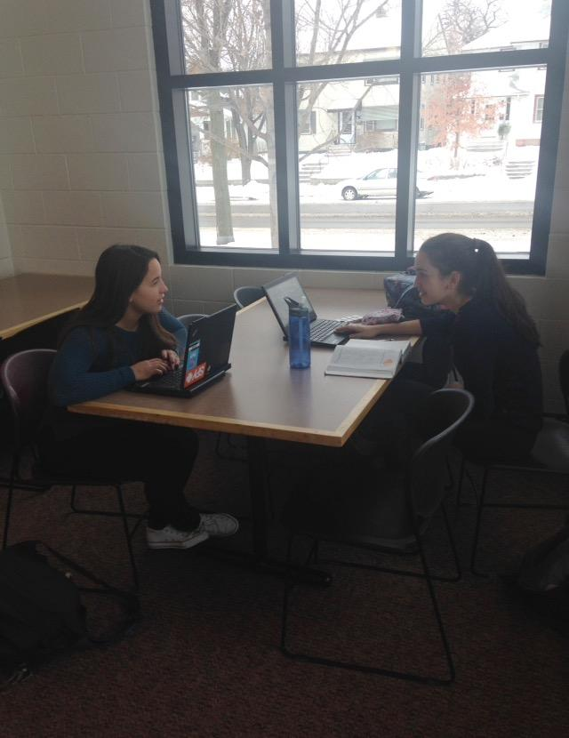 """Sophomores Maria Perkkio and Genevieve Zanaska work in the lunch room during their free period. """"It's nice to be able to work [in the lunch room] because sometimes the benches get really loud,"""" Perkkio said."""