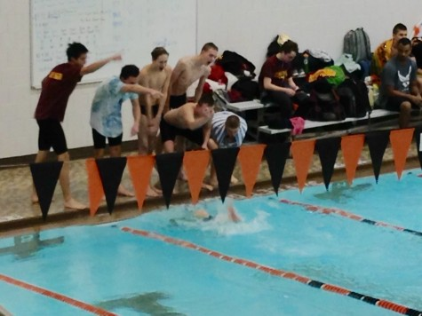 The boys varsity swim team cheers on their teammate during the 300m breast-fly relay.