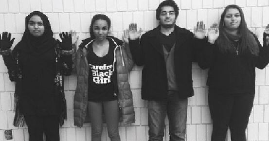"""standing in solidarity with Ferguson, seniors Aliza Rahman, Mansuda Arora, Asad Masood, and Alexis Irish raise their hands to sybolize the common rally cry """" Hands up, don't shoot."""""""