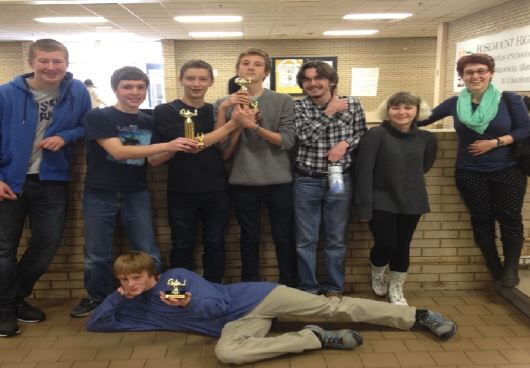 Member of the Quiz bowl team pose with their trophies at the Rosemount Annual Thumb-Racing Academic Competition Event after qualifying for nationals. Left to right: freshman Peter Blanchfield, sophomore Jack Indritz, freshman Jack Hermann, sophomores Ewan Lang, Cole Thompson, and Phoebe Pannier, junior Netta Kaplan, and sophomore Cole Staples (on ground).