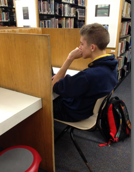 """Junior Sam Matenaer takes advantage of the isolation provided by the cubby desks in the library. """"It's not a table, so I'm sitting alone, so it's easier to focus on my work,"""" he said."""