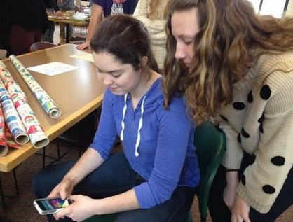 "Juniors Alena Porter and Hallie Sogin play a round of Trivia Crack before advisory. ""People got me started on it, and now I can't stop,"" Sogin said. The game is ranked #1 in the Apple Store and #4 on Google Play."