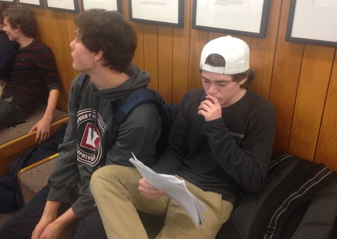 """Sophomore Jack Johnston reads his teacher comments while sitting on the sophomore benches. """"It helps me set goals for how to get better during the second semester,"""" Johnston said."""