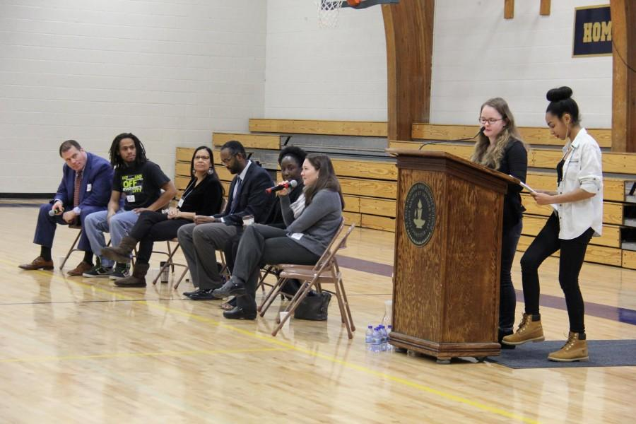 Seniors Evva Parsons and Mansuda Arora introduce the panel of Paul Applebaum, Chris Lollie, Lonna Stevens Hunter, Jaylani Hussein, Ashley Johnson, and Sarah Herder at the MLK assembly.