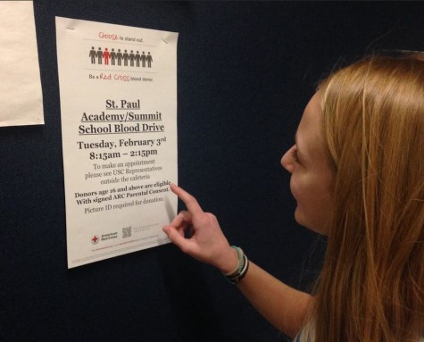 "Sophomore Ella Matticks checks out a Blood Drive poster in the athletic hallway, one of many posters posted around school. ""I think [the Blood Drive] is a great thing our school does,"" Matticks said."