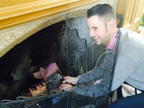 Upper School history teacher Aaron Shuler pretends to throw a book into the fireplace, something highly unusual of him. Something else that he doesn't usually do is hand out insider teacher hacks to students.