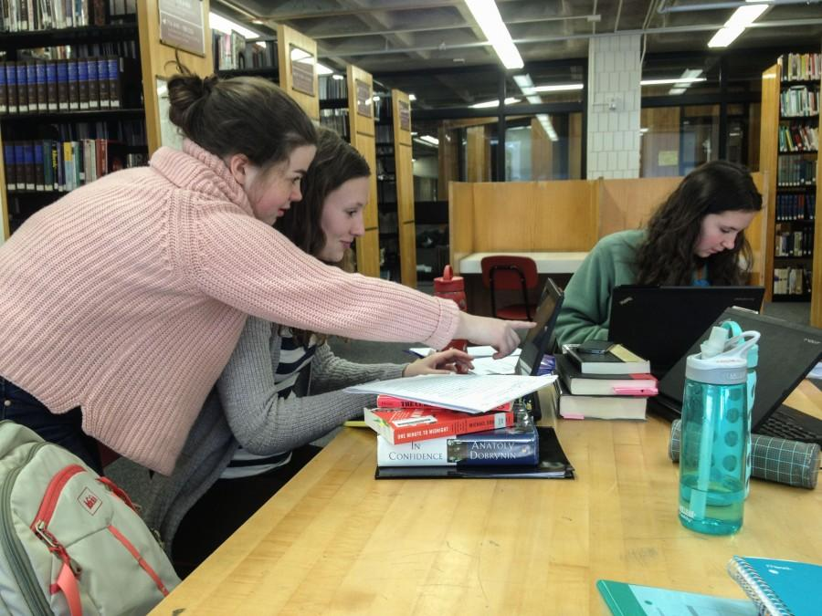 """Junior Claire Walsh gives junior Hallie Sogin some last minute feedback on her history paper. """"I think it's fun to read other people's papers because you get to see what they're interested in,"""" Sogin said. Papers were due on Feb. 11 and 12."""