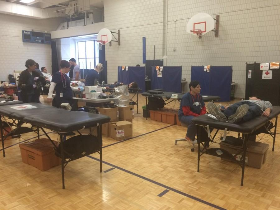 """Red Cross workers collect blood donations in the small gym on Feb. 3. """"It felt good, aside from a little wooziness. I'm happy I did it,"""" sophomore Joel Tibbetts said. The drive collected 31 units of blood."""