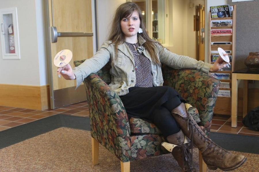 "Junior Ingrid Topp-Johnson poses with some of her recent mixtapes. ""When I am making a playlist, I usually come up with a very specific idea and then sit down at a computer and create it within half an hour,"" Topp- Johnson said."