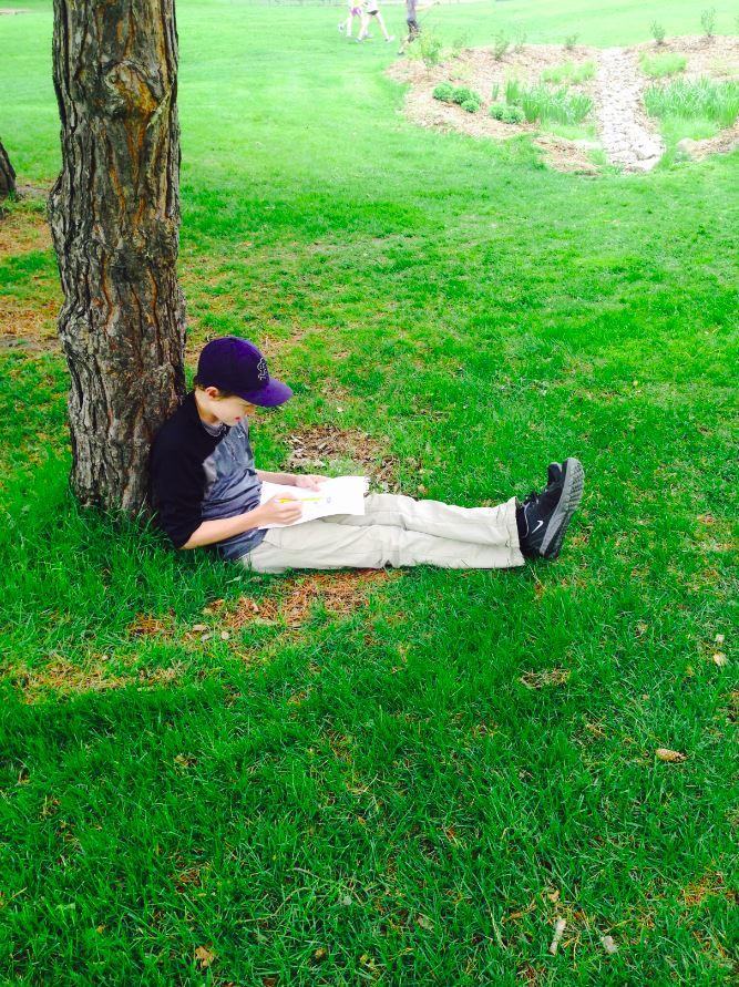 """Freshman Web Lehmann  sits under a tree while studying. """"I like to go outside while cramming for finals because it gets stuffy inside and it's nice to get fresh air,""""  Lehmann said."""