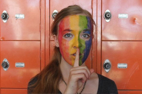 "Junior Miriam Tibbetts poses for the National Day of Silence on Apr. 17 with a finger over her mouth. This action symbolizes the quiet that is used to make a bigger sound. The face paint shows support for the LGBTQ+ community. ""It's important to use Day of Silence to pay tribute to those who have been silenced, to help show people they aren't alone in feeling silenced, and encourage change to help people regain their voices,"" senior GSA Co-President Maggie Clark said."
