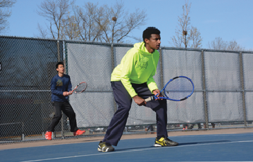 JUnior matti solomon (centered) plays in a doubles match here with senior Elliot Tong. Solomon participated in section play and was the only varsity member to make it to the second round