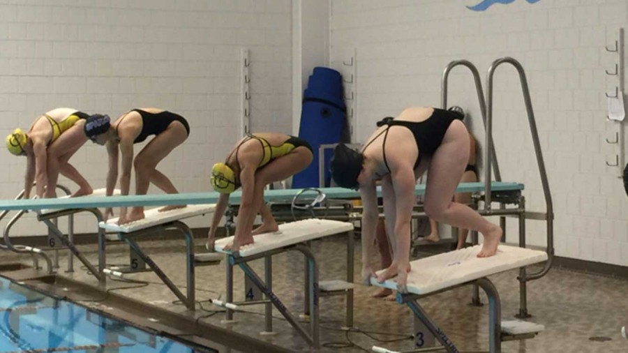"SPARKS SWIM AND DIVE take position on the starting block before entering the pool for a race. ""There are nine teams in our division and we normally place 4th, but this year I think we can place 3rd,"" senior Maya Smith said."