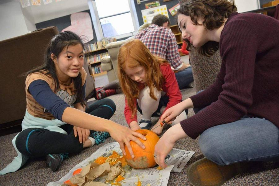 Seniors Elena Youngdale and Maggie Vlietstra work together with their kindergartner to carve a pumpkin.