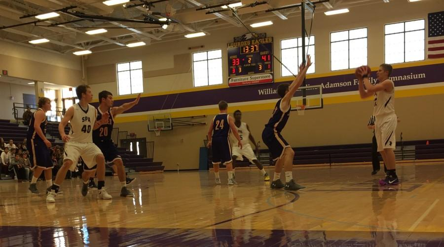 Senior Charlie Hooley fakes a pass to the post in the Spartan's 58-55 Saturday win against the Lourdes Eagle's.