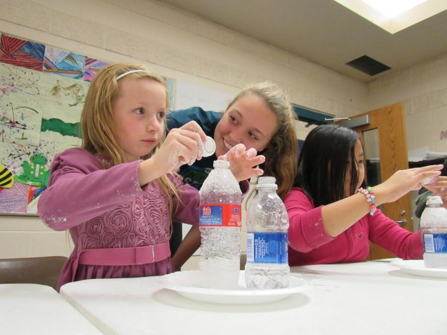 Sophomore+Greta+Sirek%2C+a+volunteer+at+Conway+Recreation+Center%2C+helped+children+conduct+volcano+experiments+with+baking+soda+and+vinegar.+%E2%80%9CI+love+seeing+the+kids+smile+and+it%E2%80%99s+fun+when+I+come+back+after+a+while+and+the+kids+run+up+to+me+and+give+me+a+hug%2C%E2%80%9D+Sirek+said.+