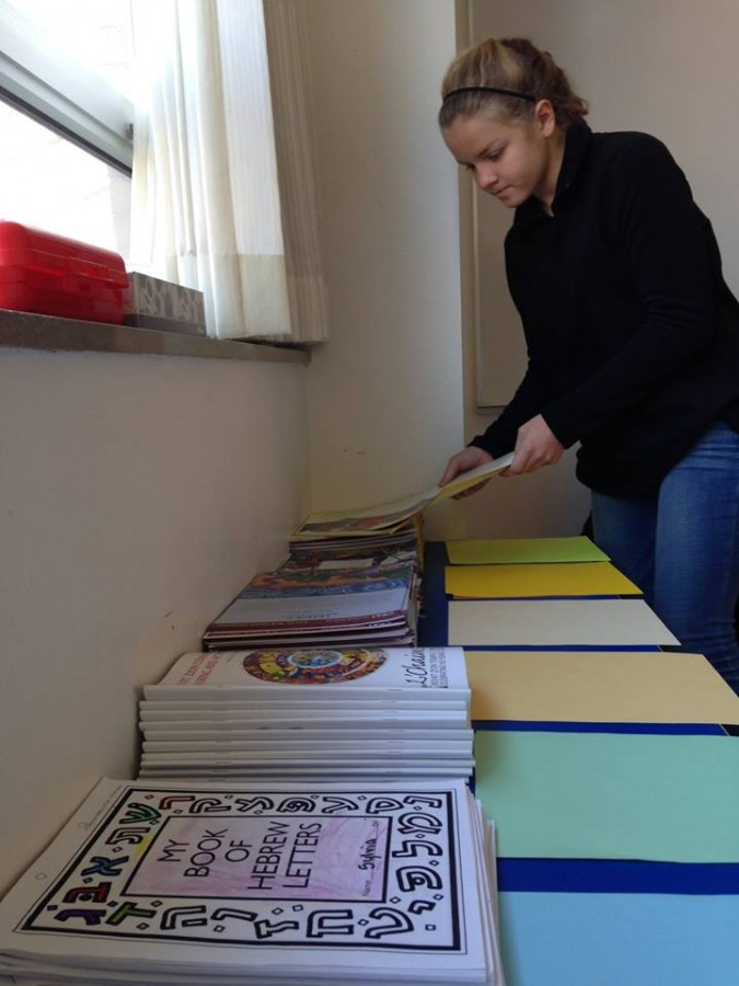 """Sammy Reis organizes the material she uses in her first grade classroom. """"I mostly teach the kids how to be Jewish and doing good deeds. We go over some things in the torah, we read these mini magazine articles and then do an activity involving that,"""" she said."""