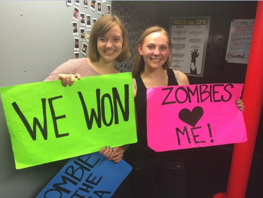 Seniors Meghan Joyce and Calla Saunders hold up signs although they didn't escape in time.