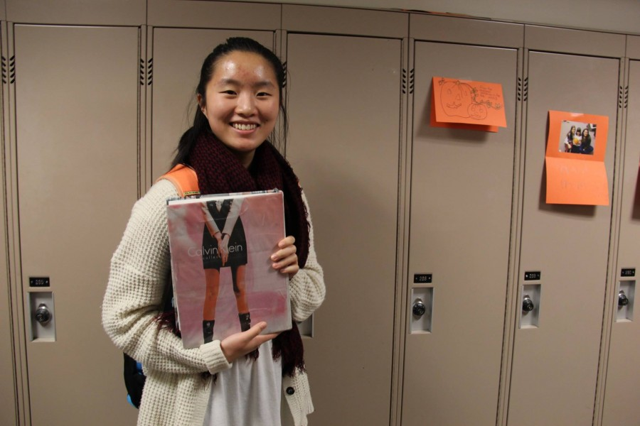 """SENIOR CHRISTINE LAM poses with her textbook. """"It's really interesting, because I can sometimes read the articles… the section I pulled out was about fashion, which is interesting to me."""" Lam said."""