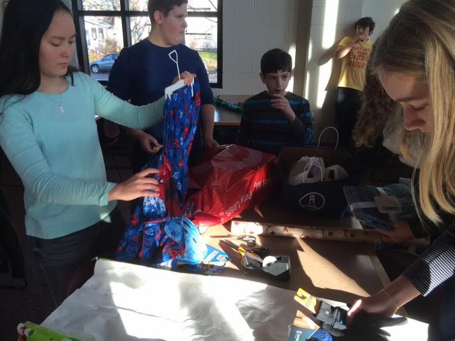 Freshmen Gemma Yoo, Riley Tietel, Isaac Fink, and Maggie Hlavka wrap gifts for 4-year-old Jayce. Jayce wanted pajamas and socks, and really likes Spider-Man.