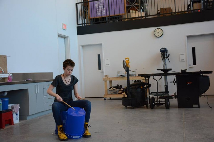 """Senior Alice Tibbetts taps out a rhythm on an overturned plastic bucket. """"We don't play pop or rock, but really weird world music that has a lot of complicated sounding rhythms. A bunch of people play different simple rhythms that twine together and sound cool,"""" Tibbetts said."""