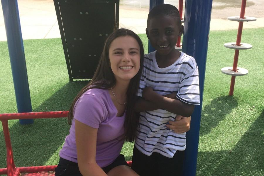 Sophomore Val Hart poses with one of the kids she was volunteering with.