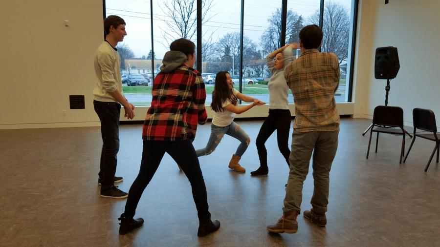 Senior directors Jack Romans (left) and Maggie Vlietstra (right, standing) bond with cast members during a rehearsal in the Driscoll Family Commons. Leading up to the performance, Romans said,