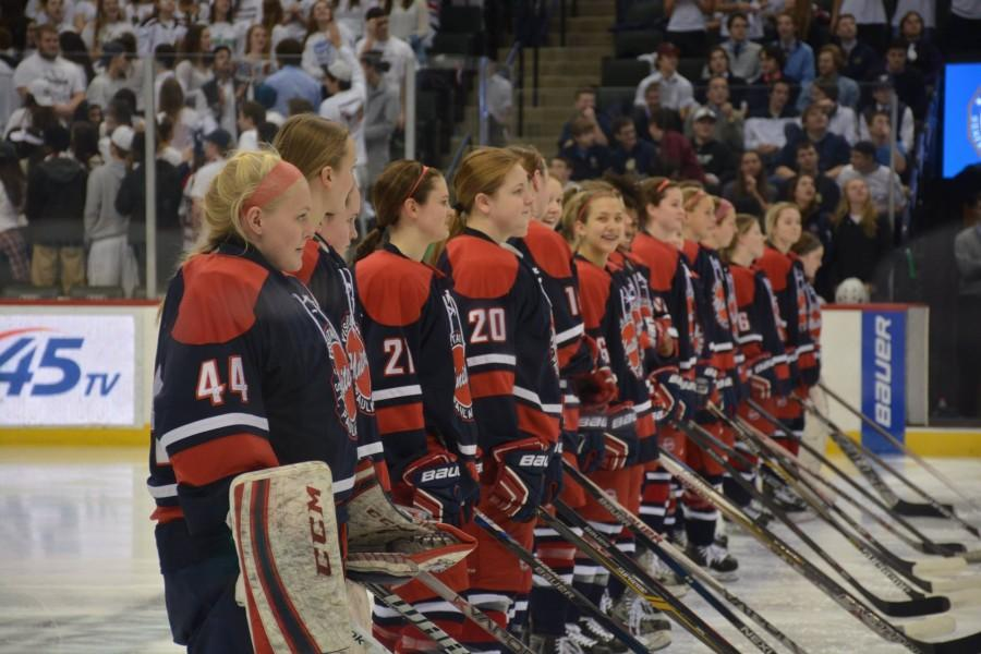 United players wait for Warroad to finish their player introductions.