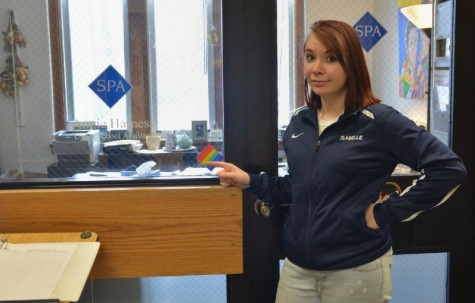 Junior Isabelle Bukovsan points to one of the old rainbow stickers given to teachers and staff to designate their offices and classrooms as safe spaces for LGBTQ+ youth.