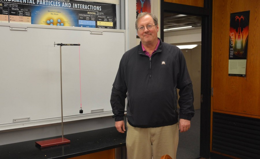 """Jim Tisel stands by a pendulum, the apparatus Tisel used to study the power of questions in the classroom.. """"A driving motivation for me as an educator has been 'what motivates students to ask questions',"""" Tisel said."""