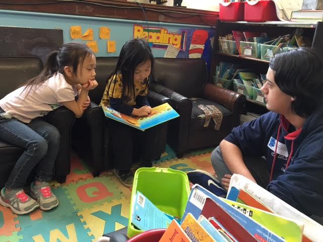 Freshman Daven Rock listens intently to first grade students from the Community School of Excellence.