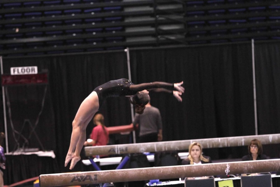 Junior+Raegan+Small+executes+a+back-handspring+and+switch-leap+on+beam.