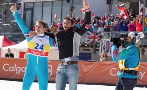 "Michael ""Eddie"" Edwards (Taron Egerton) and Bronson Piery (Hugh Jackman) pose after Eddie's 70m jump at the 1988 Winter Olympics."