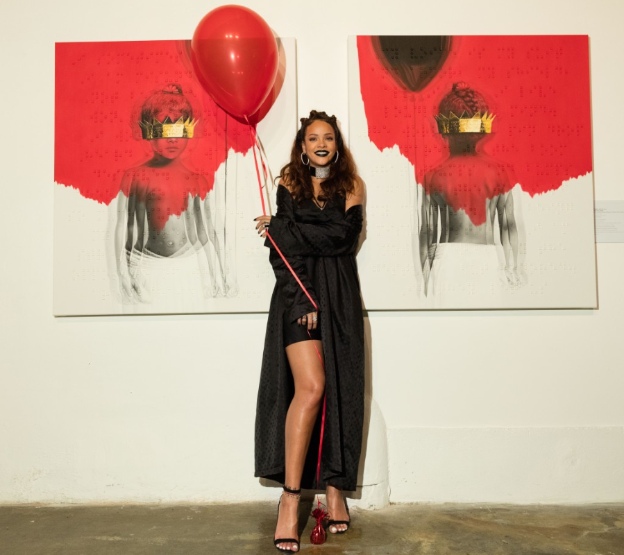 Rihanna holds up a red balloon, and poses in front of the album's artwork, at the cover art reveal.
